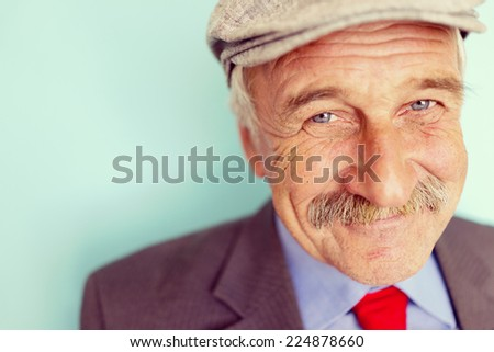 Portrait of a smiling and confident senior good looking business man with hat - stock photo