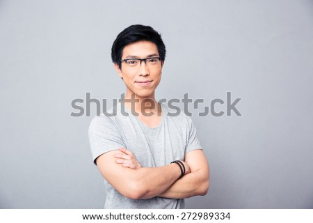 Portrait of a smiling asian man in glasses standing with hands crossed over gray background. Looking at camera - stock photo