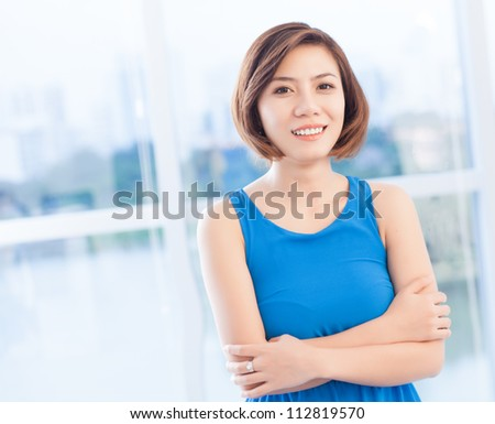 Portrait of a smiling Asian woman wearing blue dress - stock photo