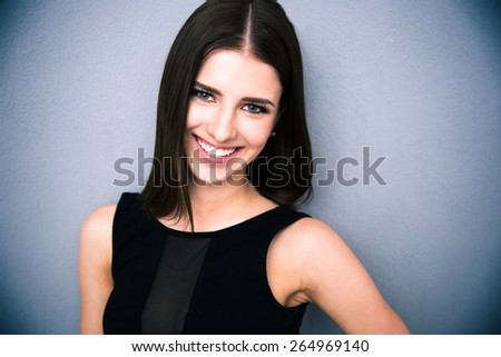 Portrait of a smiling attractive looking at the camera. Wearing black dress. Posing over grey background - stock photo