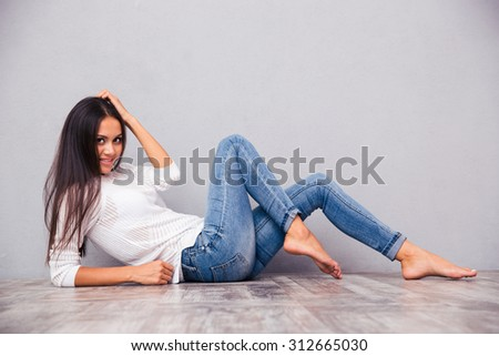Portrait of a smiling attractive woman lying on the floor on gray background - stock photo