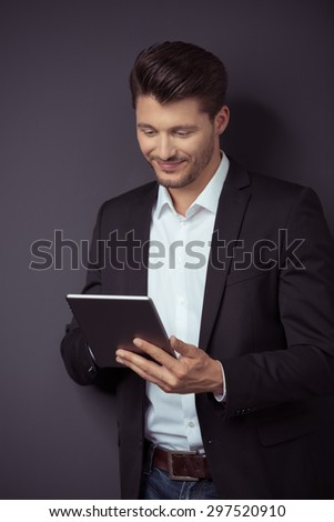 Portrait of a Smiling Attractive Young Businessman Using his Portable Tablet Computer Against Gray Wall Background. - stock photo