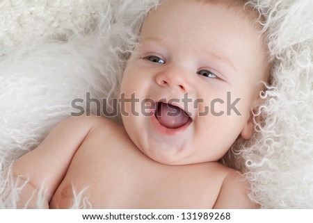 Portrait of a smiling baby close-up. Eyes in the direction of. - stock photo