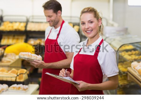 Portrait of a smiling baker with her colleague in bakery - stock photo
