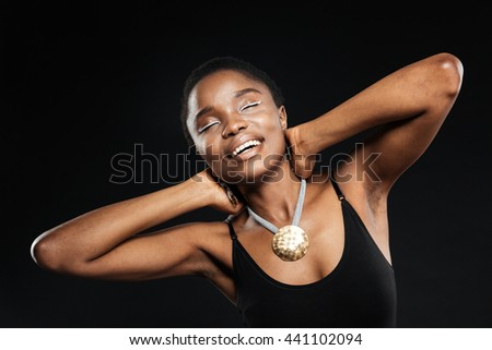 Portrait of a smiling beautiful african woman posing with eyes closed in studio isolated on the black background - stock photo
