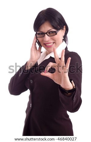 Portrait of a smiling beautiful business woman talking at the phone and showing the perfect sign isolated over white background