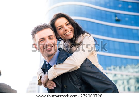 Portrait of a smiling beautiful couple outdoors with glass building on background - stock photo