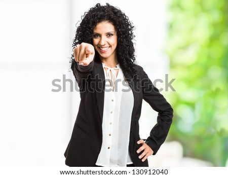 Portrait of a smiling beautiful woman pointing her finger at you - stock photo