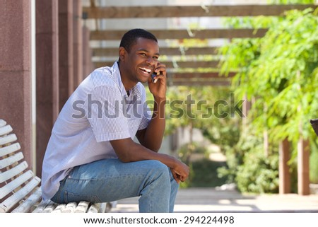 Portrait of a smiling black guy talking on mobile phone outside - stock photo