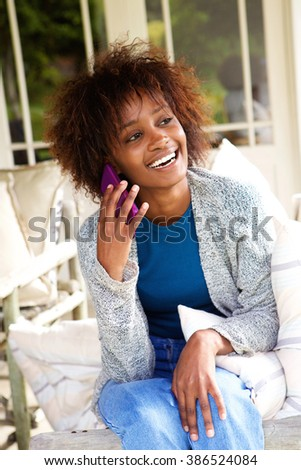 Portrait of a smiling black woman talking on mobile phone