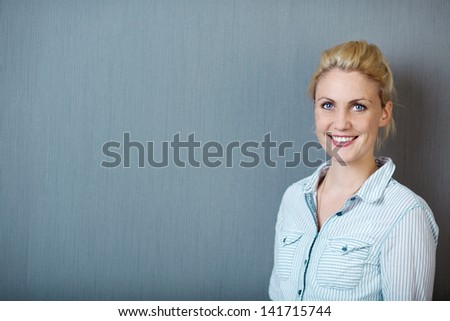 Portrait of a smiling blond woman standing against blue background - stock photo
