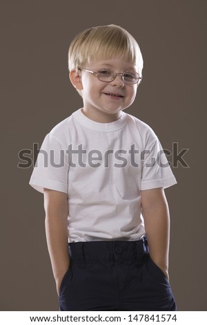 Portrait of a smiling blonde haired boy wearing glasses against gray background - stock photo