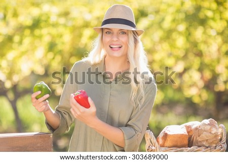 Portrait of a smiling blonde holding red and green peppers - stock photo