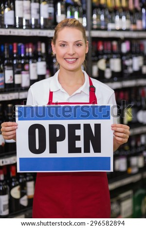 Portrait of a smiling blonde woman holding a sign in supermarket - stock photo