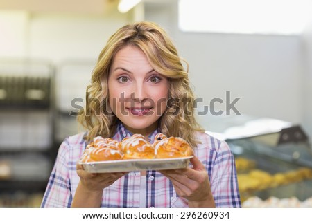 Portrait of a smiling blonde woman showing a pastry in bakery - stock photo