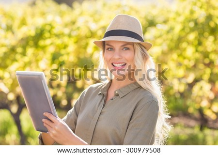 Portrait of a smiling blonde woman using a tablet - stock photo