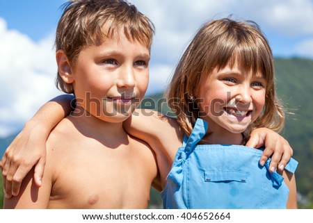Portrait of a smiling boy and girl in a friendly embrace each other's shoulders