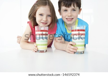 Portrait of a smiling boy and girl sitting at table with colorful glasses - stock photo
