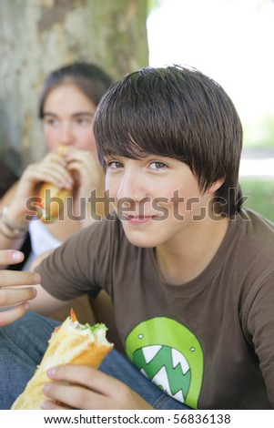 Portrait of a smiling boy eating sandwiches - stock photo