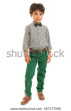 Portrait of a smiling boy in a checkered shirt, green trousers and smart shoes against a white background