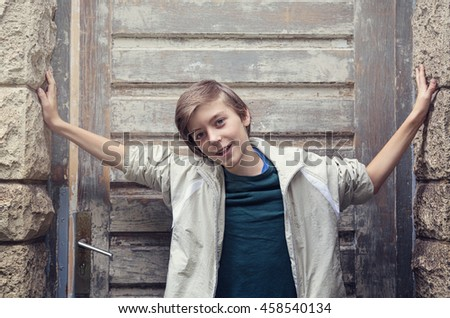 portrait of a smiling boy standing in front of an old entrance - stock photo