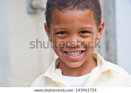 portrait of a smiling boy wearing a school uniform in the caribbean - happy to be home from school - stock photo