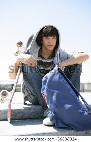 Portrait of a smiling boy with a skateboard and a backpack - stock photo