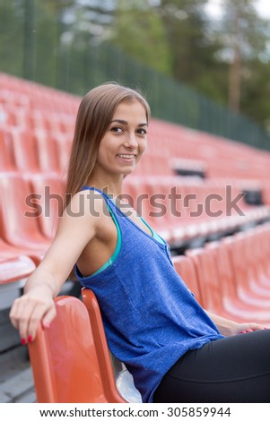 Portrait of a smiling brunette girl at the stadium. - stock photo