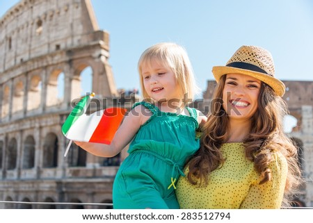 Portrait of a smiling brunette mother wearing a hat is holding her blonde daughter who is waving an Italian flag in the summer. In the distance, the Colosseum. - stock photo