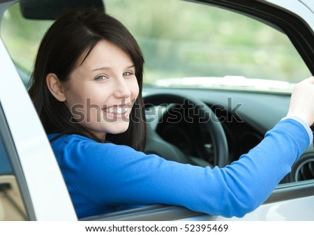 Portrait of a smiling brunette woman driving - stock photo