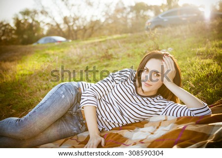 Portrait of a smiling brunette woman relaxing outdoors on picnic in a autumn day - stock photo