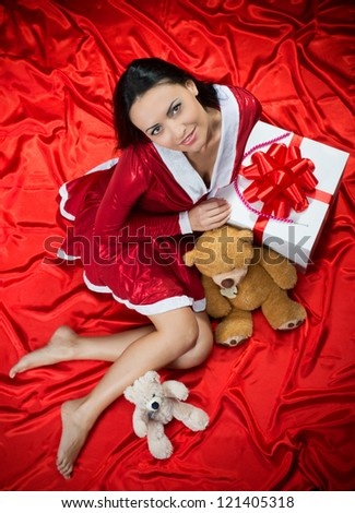 Portrait of a smiling brunette woman with toys and Christmas present on red background, view from above