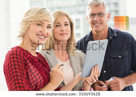 Portrait of a smiling business team holding a tablet at office