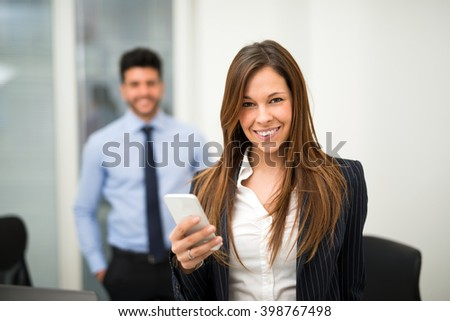Portrait of a smiling business woman using her smartphone - stock photo