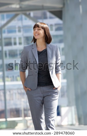 Portrait of a smiling business woman walking - stock photo