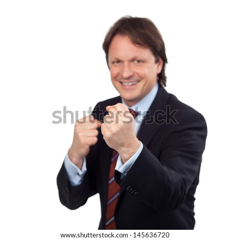 portrait of a smiling businessman balling his fists - stock photo
