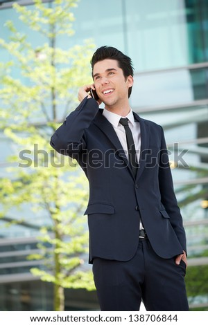 Portrait of a smiling businessman communicating on mobile phone outdoors - stock photo