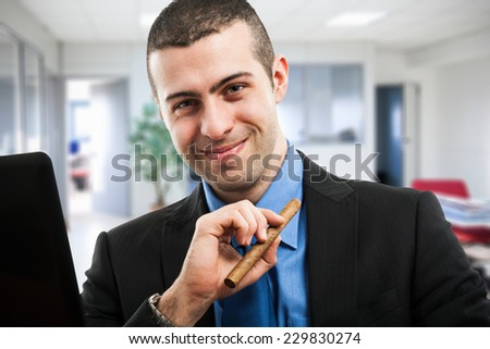 Portrait of a smiling businessman holding a cigar - stock photo