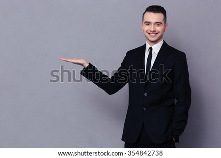 Portrait of a smiling businessman holding copyspace on the palm over gray background - stock photo