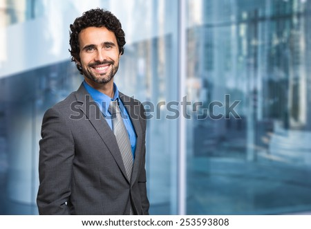 Portrait of a smiling businessman in front of a blue modern background - stock photo