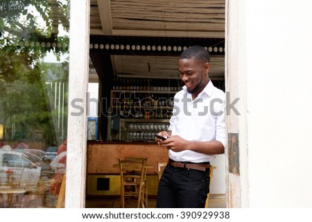 Portrait of a smiling businessman looking at mobile phone - stock photo