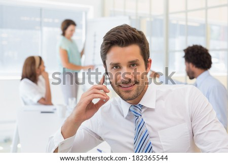 Portrait of a smiling businessman on call with colleagues in background at the office - stock photo