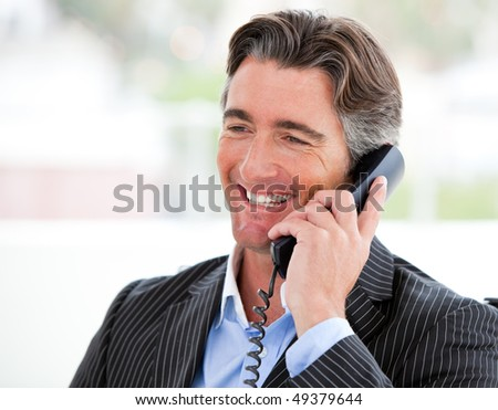 Portrait of a smiling businessman on phone in his office - stock photo