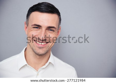 Portrait of a smiling businessman over gray background. Looking at camera