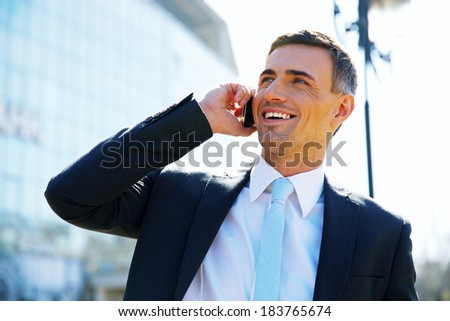 Portrait of a smiling businessman talking on the phone at street - stock photo