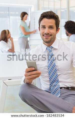 Portrait of a smiling businessman text messaging with colleagues in background at the office