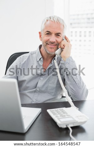 Portrait of a smiling businessman using telephone in front of laptop at office desk