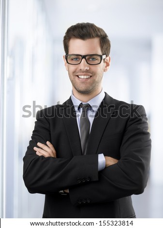 Portrait of a smiling businessman with arms crossed standing in office - stock photo