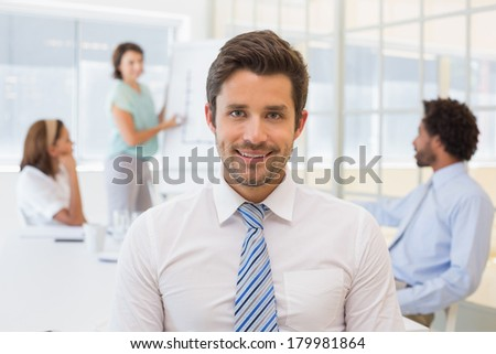 Portrait of a smiling businessman with colleagues in meeting in background at the office - stock photo
