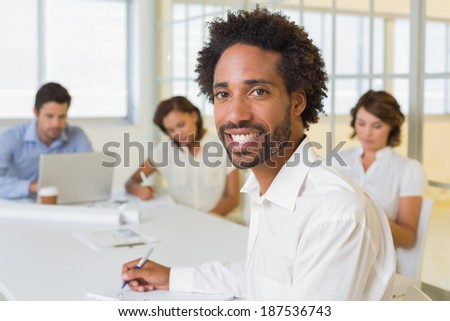 Portrait of a smiling businessman with colleagues in meeting in background at the office